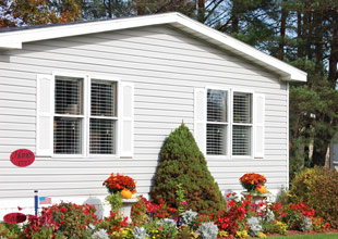 White manufactured home with flowers in Caro, Michigan